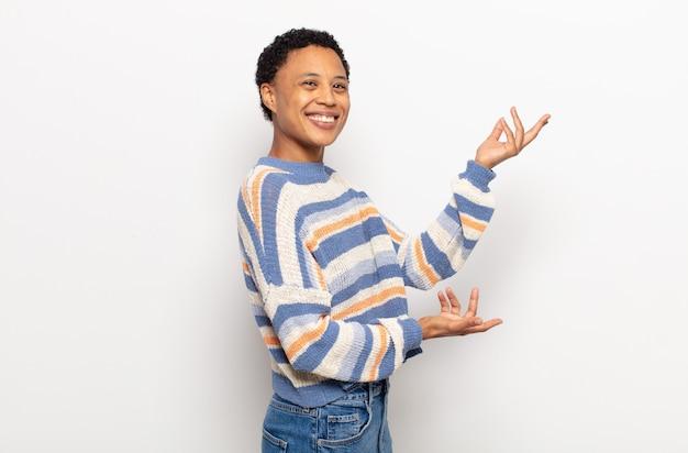 誇らしげに自信を持って笑って、幸せで満足しているアフロの若い黒人女性