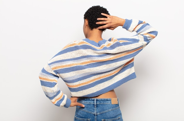 Афро молодая темнокожая женщина думает или сомневается, почесывает голову, чувствует озадаченность и замешательство, вид сзади или сзади