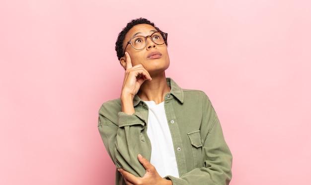 集中した表情のアフロ若い黒人女性、疑わしい表情で不思議に思って、見上げて横に