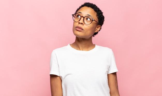 Афро молодая темнокожая женщина с обеспокоенным, смущенным, невежественным выражением лица, глядя вверх, чтобы скопировать пространство, сомневаясь