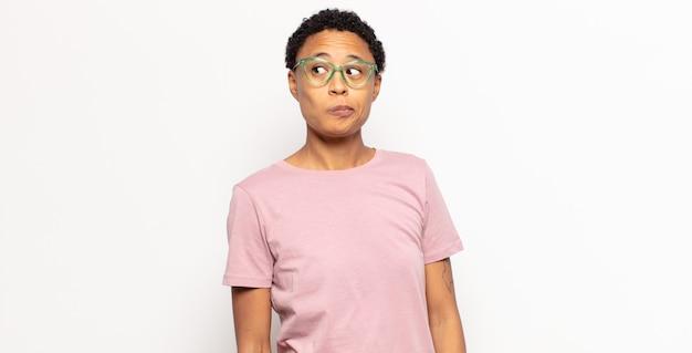 不思議に思って、幸せな考えやアイデアを考えて、空想にふけって、横のスペースをコピーしようとしているアフロの若い黒人女性