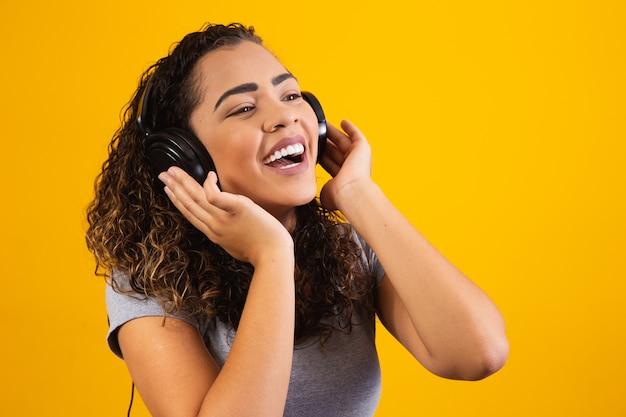 音楽を聴いている彼女のヘッドフォンを持つアフロ少女。閉じる