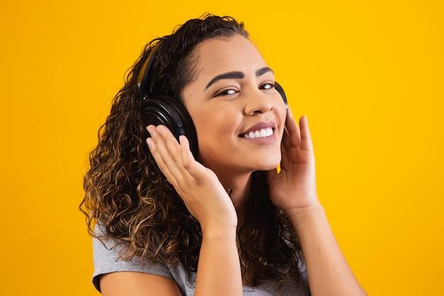 Афро молодая девушка с наушниками, слушая музыку. крупным планом