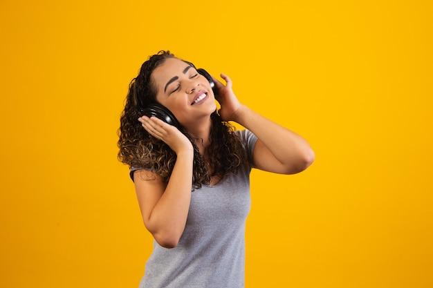 音楽を聴いている彼女のヘッドフォンを持つアフロ少女