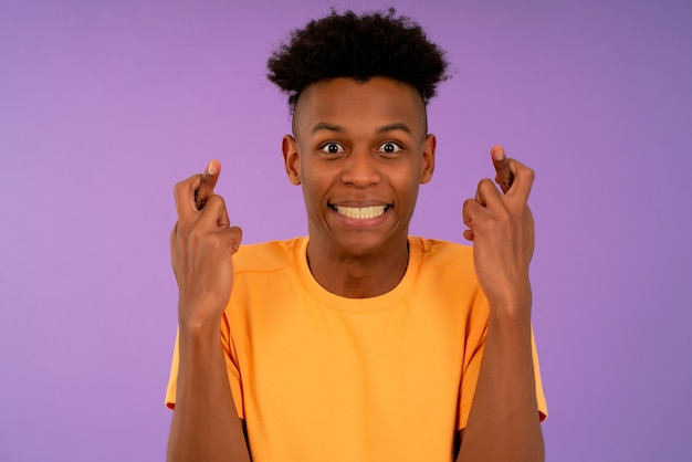 Afro giovane incrociando le dita augurando buona fortuna.