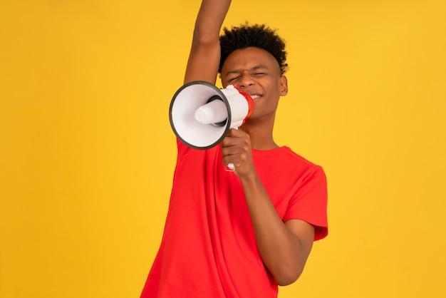 黄色の背景に立っている間、彼の声を上げるためにメガホンを使用しているアフロの若い男。広告とプロモーションのコンセプト。