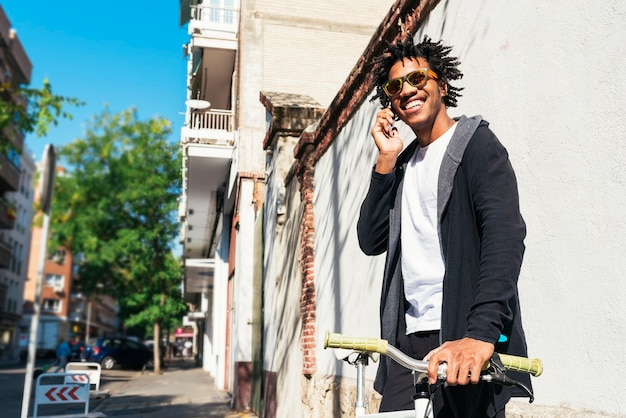 通りで携帯電話と固定ギア自転車を使用しているアフロの若い男。