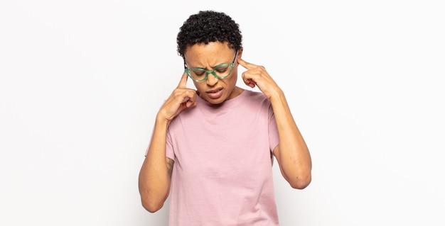 怒り、ストレス、イライラしているように見えるアフロの若い女性は、耳をつんざくような音、音、または大音量の音楽で両耳を覆っています