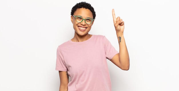 Afro young woman smiling cheerfully and happily, pointing upwards with one hand to copy space