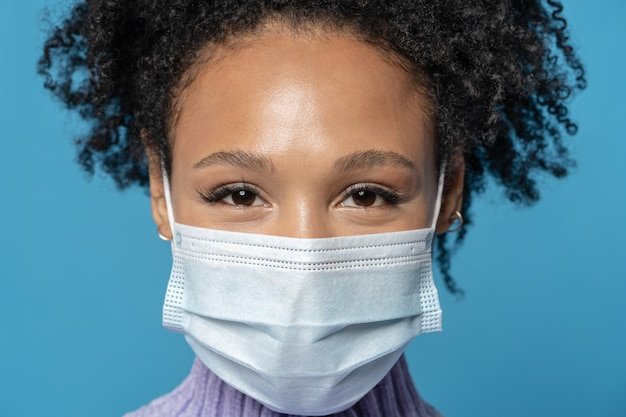 Afro young woman with curly hair looking at camera wears protective medical mask being on quarantine