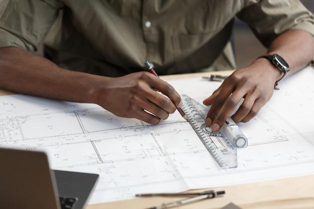 Афроамериканский архитектор, работающий в офисе с проектировщиком, проверяет эскиз архитектурного плана ...