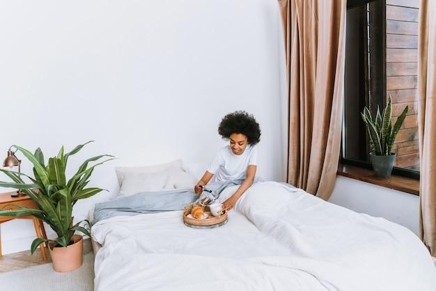 집에서 침대에서 쉬고 있는 아프리카계 미국인 소녀 침대에서 아침을 먹고 집에서 편안한 아름다운 여자