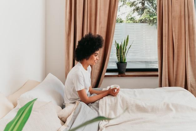 집에서 침대에서 쉬고 있는 아프리카계 미국인 소녀