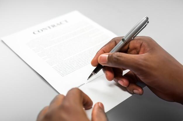 Afroamerican 남성은 대출 계약에 서명합니다. 종이에 서명하면 됩니다. 작은 글씨체에 주의하세요. 마감일을 기억하십시오.
