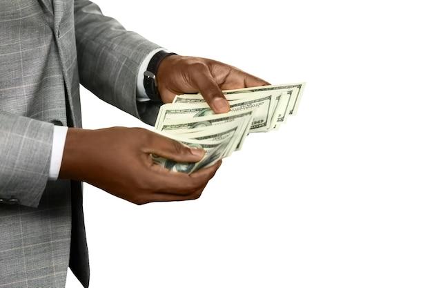 돈을 세고 있는 아프리카계 미국인 남자. 당신을 미소 짓게 만드는 종이. 그의 손에 재산입니다. 할 수 있을 때 즐기세요.