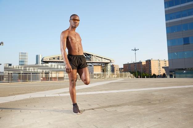 Afroamerican man doing stretching in urban environment