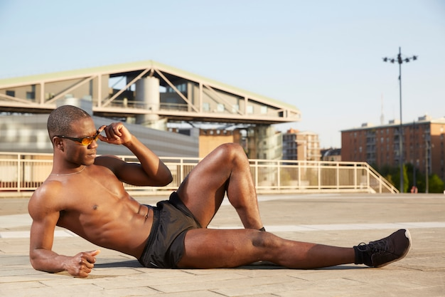 Afroamerican man doing stretching in urban environment