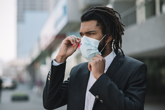 Afroamerican man fixing medical mask
