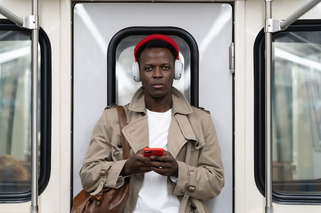 Afroamerican man stand in subway train using mobile phone listens to music with wireless headphones