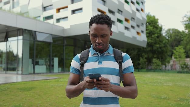 通りのオフィスセンターの近くに立っている彼が幸せに笑っているアプリを使用して電話でメッセージを読んで入力する大学の男性の背景にスマートフォンを使用してアフリカ系アメリカ人の男