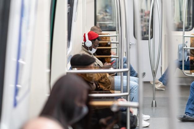 地下鉄の電車に座っているアフリカ系アメリカ人の乗客が携帯電話を使用してフェイスマスクを着用し、ヘッドフォンで音楽を聴く