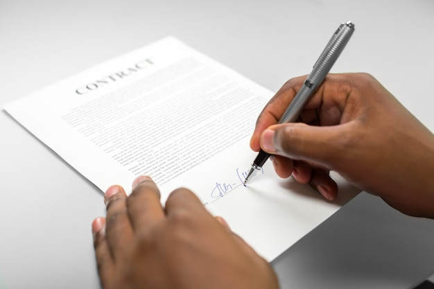 Afroamerican signing a loan contract. a delicate deal. mind the danger. where debts come from.