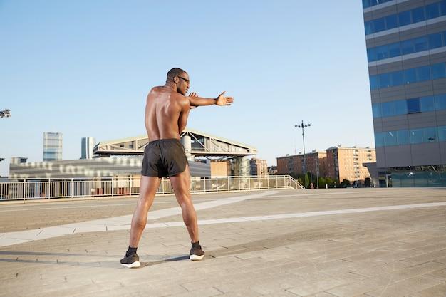 都市環境でストレッチをしているafroamerican男