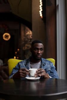 コーヒーを保持しているハンサムなafroamerican男