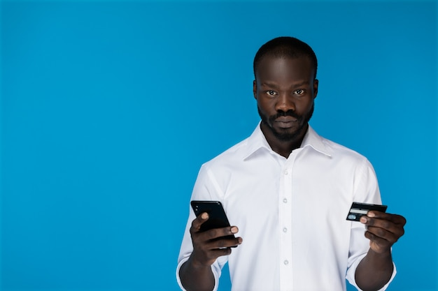 楽しみにしてafroamerican男はクレジットカードと携帯電話を手に持っています。