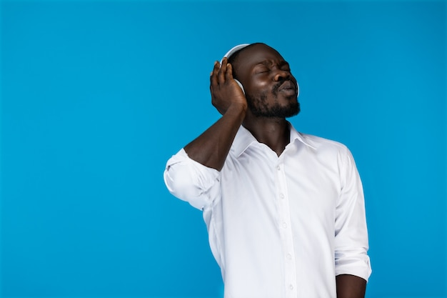 目を閉じてひげを生やしたafroamerican男は白いシャツで大きなヘッドフォンを片手で保持しています。