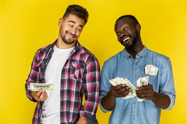 Afroamericanの男は非公式の服でヨーロッパの男とお金を共有していて、両方とも楽しそうに笑っている