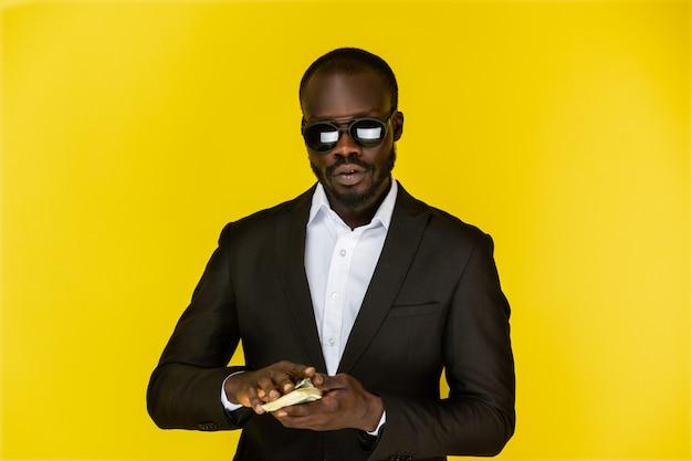 Afroamerican男はサングラスと黒のスーツを着て、両手でドルを保持しています。