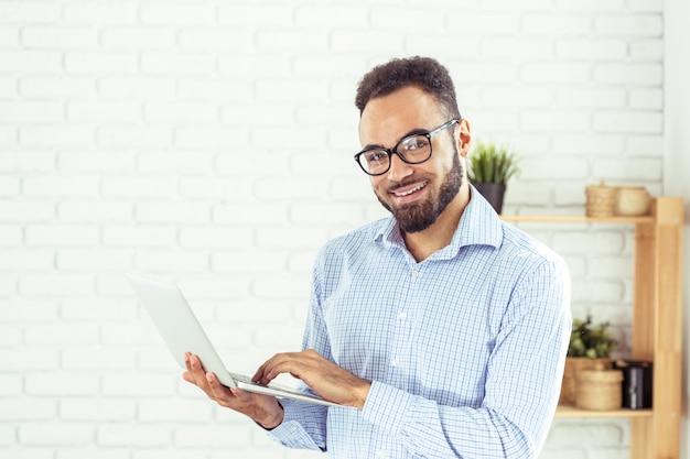 ラップトップコンピューターを使用して幸せなafroamerican男の肖像