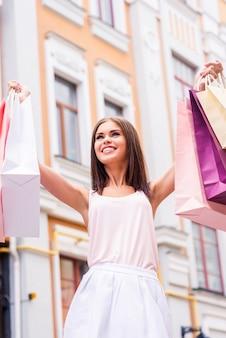 하루 쇼핑 후. 야외에 서서 쇼핑백을 들고 웃고 있는 아름다운 젊은 여성의 낮은 각도