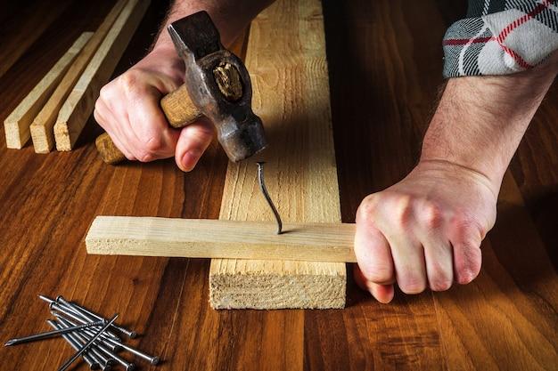 После сильного удара молотком погнулся гвоздь. крупным планом руки плотника. рабочая среда в столярной мастерской