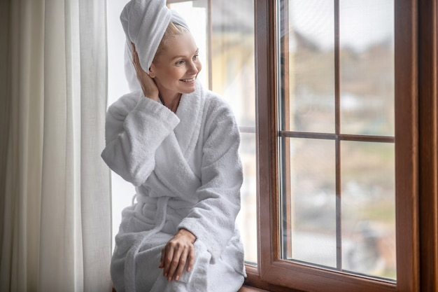 After the bath. a woman in a white robe relaxing after the bath