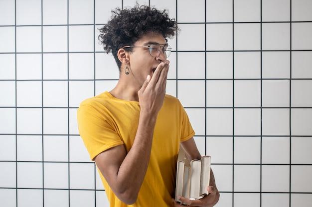 授業後。あくびをして眠そうな眼鏡をかけたアフリカ系アメリカ人の若い男