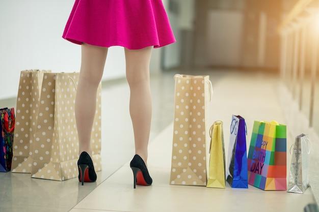 一日の買い物の後。通りを歩きながら買い物袋を運ぶ若い女性のクローズアップ