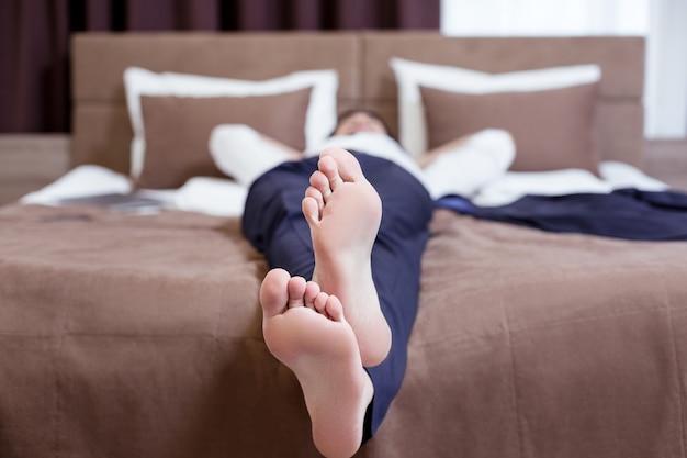 힘든 하루를 보낸 후. 어려운 근무일 후 침대에서 쉬고 좋은 피곤한 사업가의 발