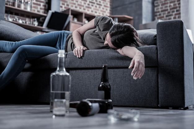 После питья. сонная пьяная молодая женщина, лежа на диване и спящая с пустыми бутылками, стоящими на полу перед ней
