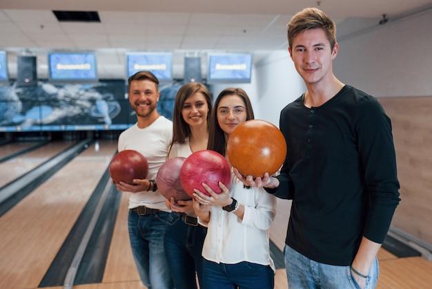 Dopo la partita. i giovani amici allegri si divertono al bowling durante i fine settimana