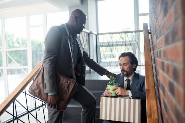 После получения избыточности. темнокожий приятный друг разговаривает с коллегой после увольнения