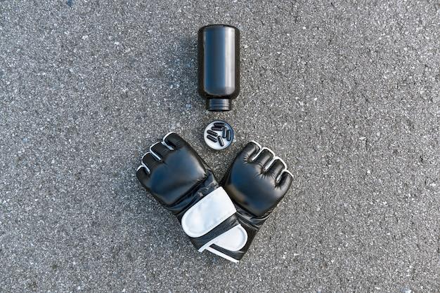 좋은 스파링 복싱 후. 아스팔트 배경에서 영양 보충제가 있는 스포츠 권투 장갑의 클로즈업