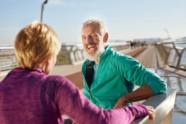 朝のランニングの後、スポーツウェアを着た陽気な成熟したひげを生やした男性が妻と話し、笑顔で