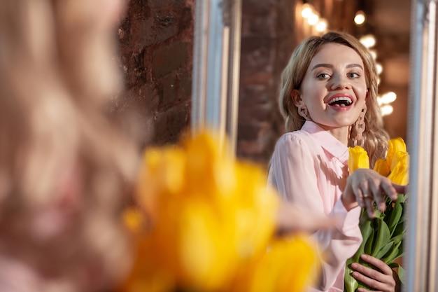 После романтического свидания. стильная сияющая блондинка чувствует себя счастливой после романтического свидания, держа в руках красивые желтые цветы
