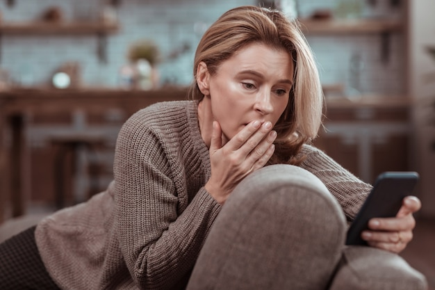 After seeing message. dark-eyed concerned woman feeling emotional after seeing message from husband
