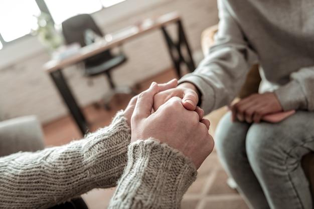 真面目な話の後。真摯に向き合った後、グレーのセーターを着た父が娘と握手