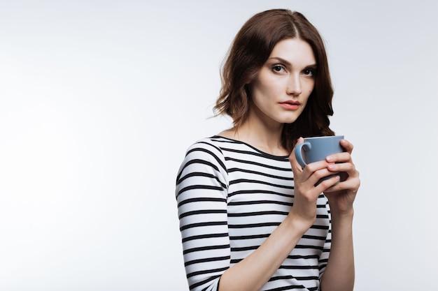 После бессонной ночи. симпатичная рыжеволосая молодая женщина держит чашку кофе и пьет его, чтобы бороться с недосыпанием