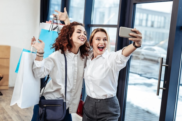 ショッピングに成功した後。買い物に成功した後、幸せな陽気なスタイリッシュな母と娘が自撮りをする