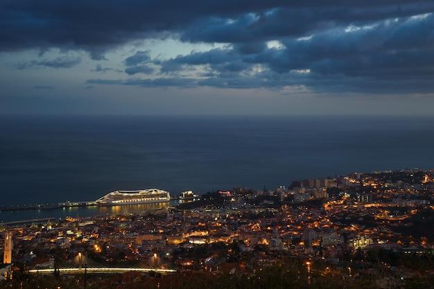 После захода солнца панорамный вид на фуншал с атлантическим океаном и круизным лайнером мадейра.